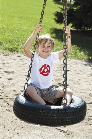 Smiling little boy sitting on a tyre swing in a park, photo