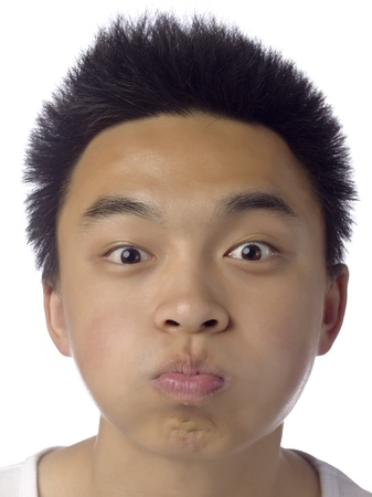 Close up image of teenage guy gesturing a funny face against white background photo