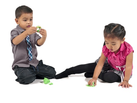 Two children playing modeling clay isolated on white Stock Photo - 17135150