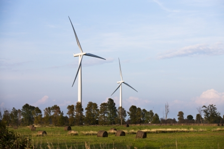 Two wind turbine in a field with blue sky in the background. Stock Photo - 17135263