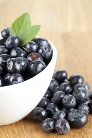 Close up image of bowl of blueberries on wooden table Zdjęcie Seryjne
