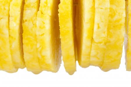 Afgeronde ananasplakken over een witte achtergrond