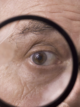 Close-up image of an eye looking on the magnifying glass photo