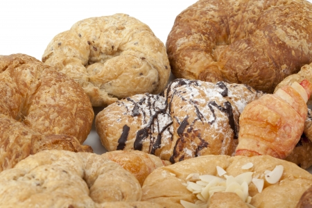 Close-up image of assortment of baked croissants bread against the white background photo