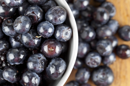 Close-up image of a bowl full of fresh blueberries on a wooden table