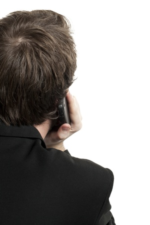 Back image of businessman talking on the phone against the white background photo