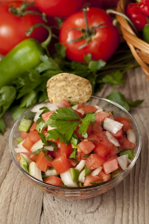 Close-up image of a bowl of Mexican salsa with chips and vegetables on the background Stock Photo - 17148677