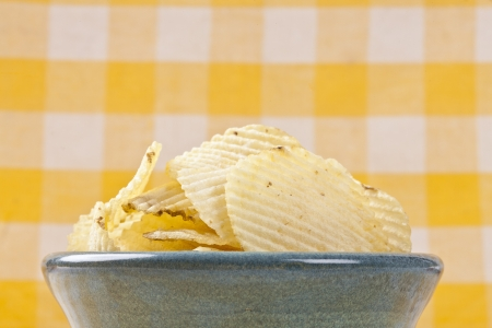 Bowl of yummy potato chips over a checkered background Stock Photo - 17148657