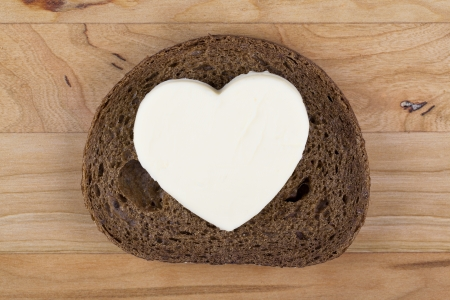 Heart shaped butter on a brown bread photo
