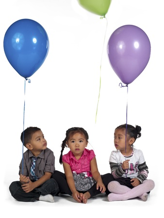 Cute little Asian children holding balloon against white background, , Kai Wall, Sienna Fulay