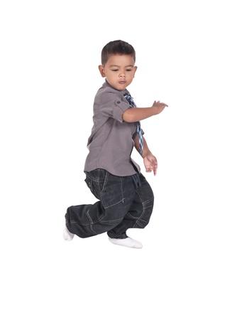 Portrait of a cute little boy dancing on a white background Foto de archivo