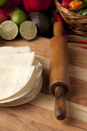 harina: Imagen recortada de una tortilla de harina y un rodillo sobre la mesa de madera