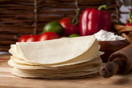 Closed up shot of folded tortillas placed near a roller