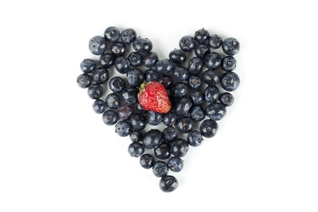 Image of heart shape made of blueberries with strawberry against white background