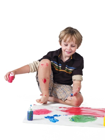 Image of a elementary boy smiling and doing painting against white background. photo