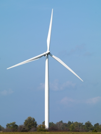 Modern wind mill in a field with clear sky in the background. Stock Photo - 17144681