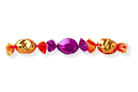 Purple hard candy in between golden hard candy over white background. photo