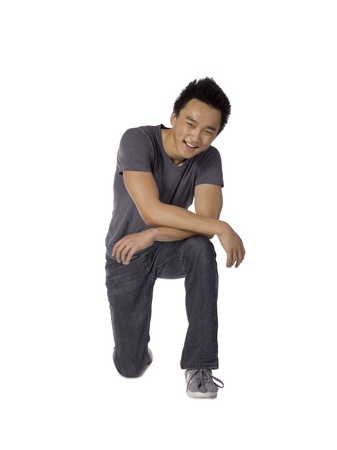 teenage guy: Portrait of smiling teenage guy kneeling on the floor against a white background