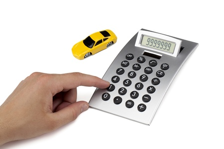 Close up image of yellow toy car with calculator against white background photo