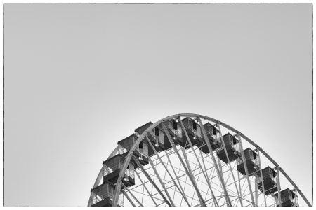 Black and white cropped image of ferris wheel at amusement park against clear sky. photo