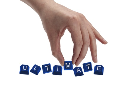 ultimate: Concept shot of hand holding keyboard keys and spelling the word ultimate.
