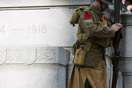 Side cropped view of a soldier with rifle standing by war memorial. photo