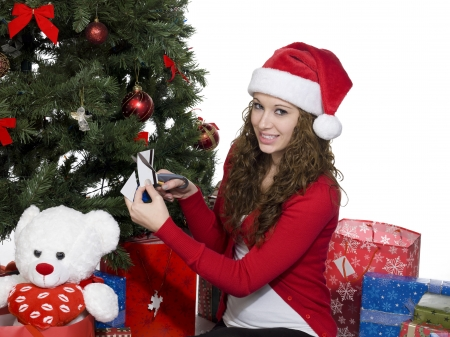 Portrait of a smiling young woman cuting credit card while sitting near Christmas tree, Model: Brittany Beaudoin