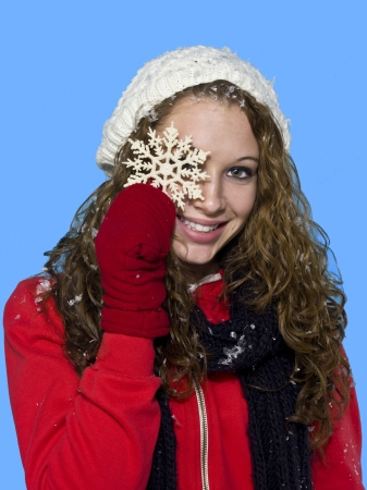 Smiling young woman holding a snowflake against turquoise background, Model: Brittany Beaudoin Stock Photo - 17287153