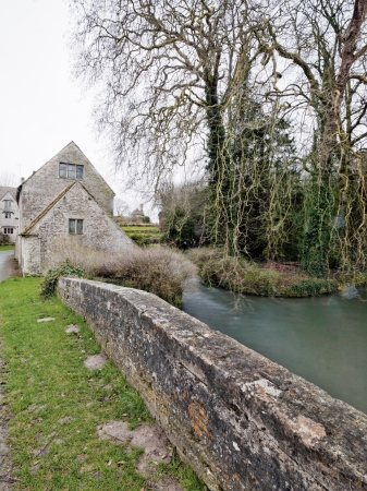 A stone wall next to a river and a willow tree Stock Photo - 17150343