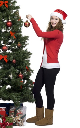 decorating christmas tree: Caucasian woman decorating a christmas tree with red balls