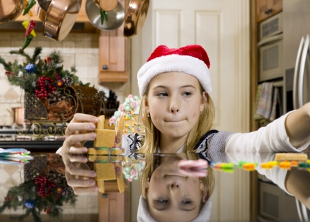 Close-up of a girl making ginger bread house on kitchen worktop. Banco de Imagens