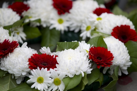 Close-up shot of red and white flower wreath at war memorial.