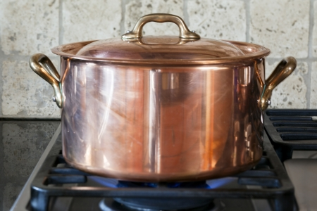 Close-up shot of copper pan on kitchen stove.