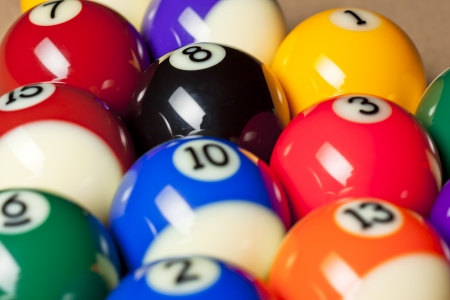 Cropped image of shiny colorful pool balls with number arranged in a row on pool table. photo