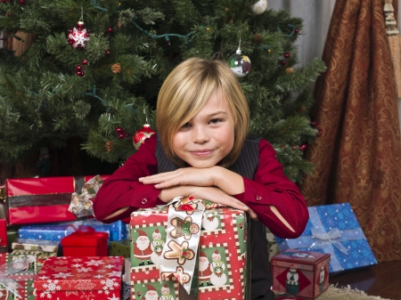 expressing: Cute boy with his christmas present looking at camera, Model: Josh Chapman