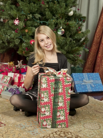 Portrait shot of a pre-adolescent girl opening a Christmas gift box with head cocked.
