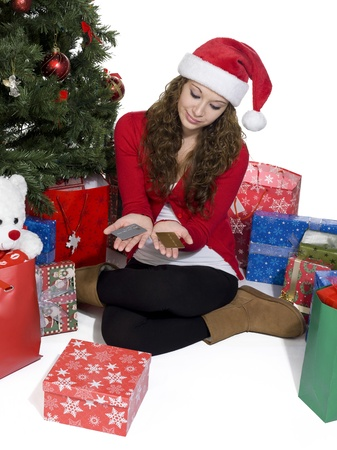 Pretty female looking at credit cards in her hand while sitting next to Christmas tree. Stock Photo - 17396169