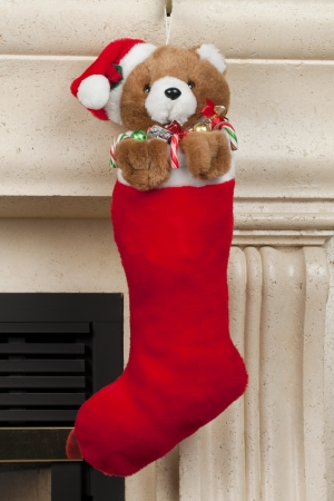 A brown teddy bear hanging over the red Christmas stocking photo