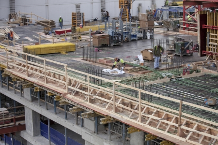 A horizontal top view image of a construction site with several male workers