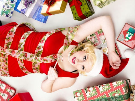decembe: Top view of a beautiful young woman with christmas candy lying on back with gift boxes on the side. Stock Photo