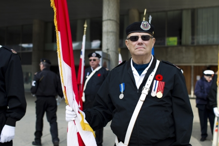 military uniform: View of a senior man holding a flag and wearing sunglasses and military uniform on remembrance sunday.