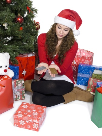 Image of a beautiful young woman with credit cards in hand sitting besides Christmas tree, Model: Brittany Beaudoin photo