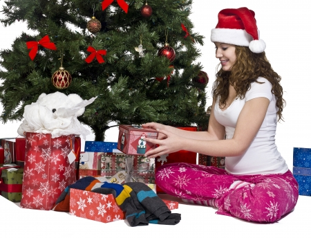 Woman in santa hat with her Christmas gift sitting near Christmas tree, Model: Brittany Beaudoin Stock Photo - 17287158