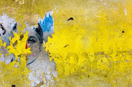 A womans face us covered in yellow paint on a wall in India