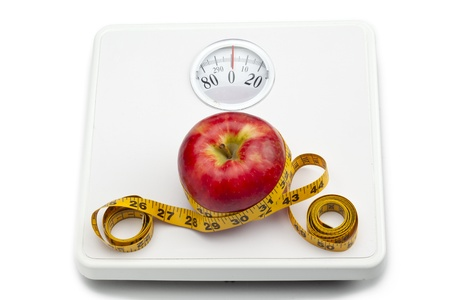 Red apple and measuring tape on the weighing scale