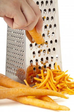 Close-up image of human hand grating carrots over the white background Reklamní fotografie