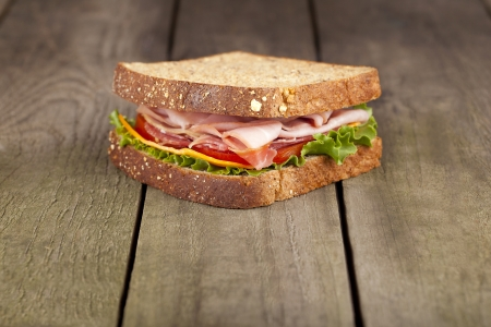 BLT sandwich on wholegrain bread on a brown background Stock Photo