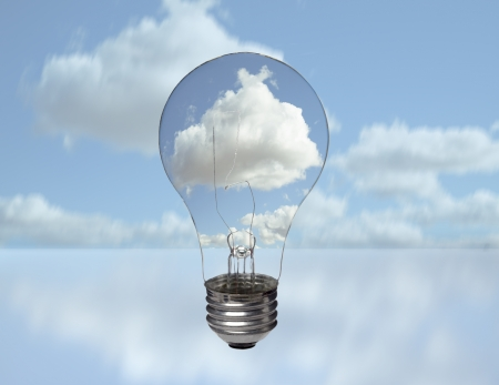 property: A clear electric light bulb against blue sky and puffy cloud background Stock Photo