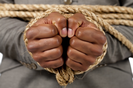 Close-up image of businessman's hand tied with rope photo