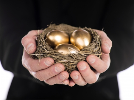Close-up shot of a businessman holding nest in hands with golden eggs. Model: Winter Bourne